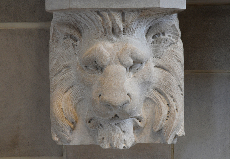 lion sculpted on fireplace mantel