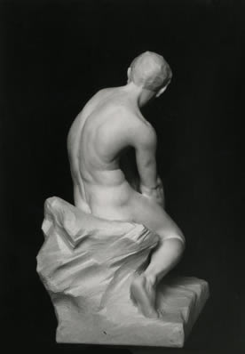 sculpture of seated boy back view