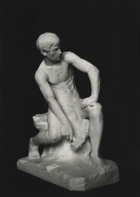 stone sculpture of seated boy